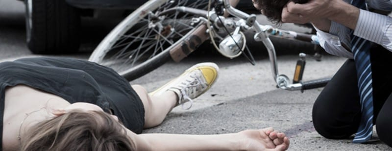 DUI manslaughter vehicle homicide |image: Woman injured lays in street with crashed bike and car nearby. Alavi & Pozzuto are compassionate trial attorneys who can help.