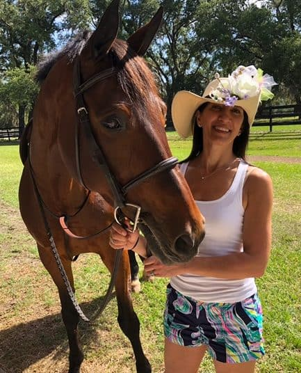 Ocala Criminal Lawyer Tania Alavi standing with horse in field at The Grand Oaks Resort near Ocala